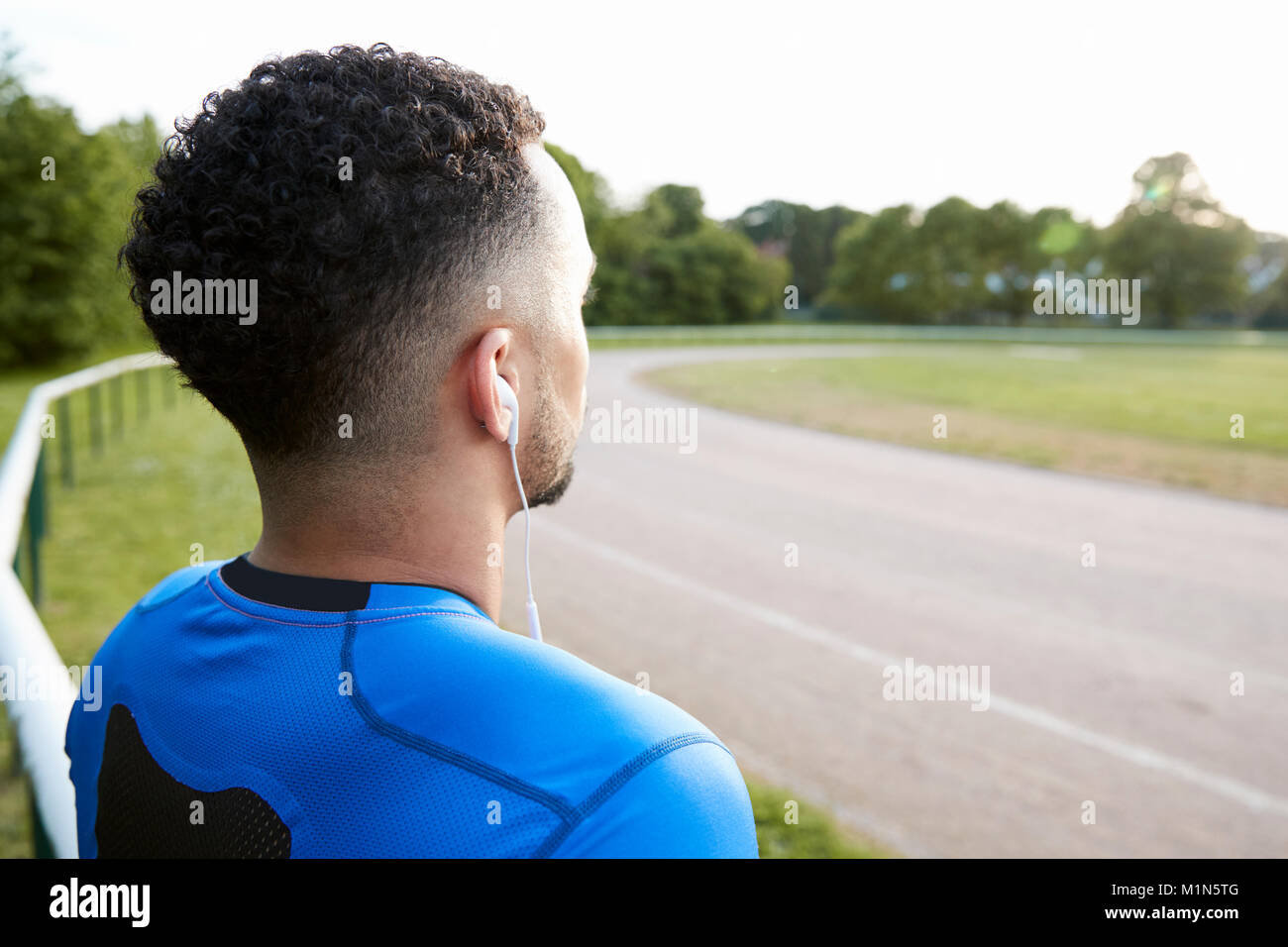 Male athlete at track looking away, close up, back view Stock Photo