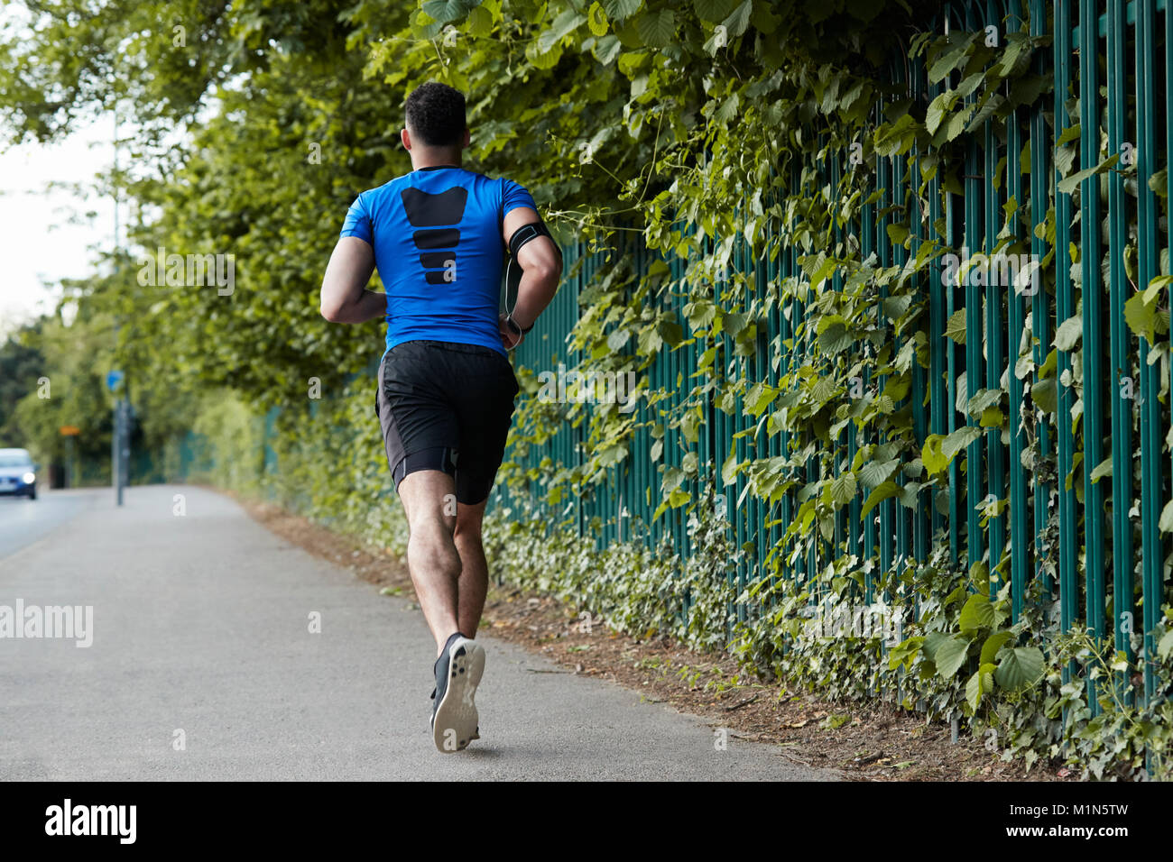 Back view of young male athlete running in the street - Stock Image