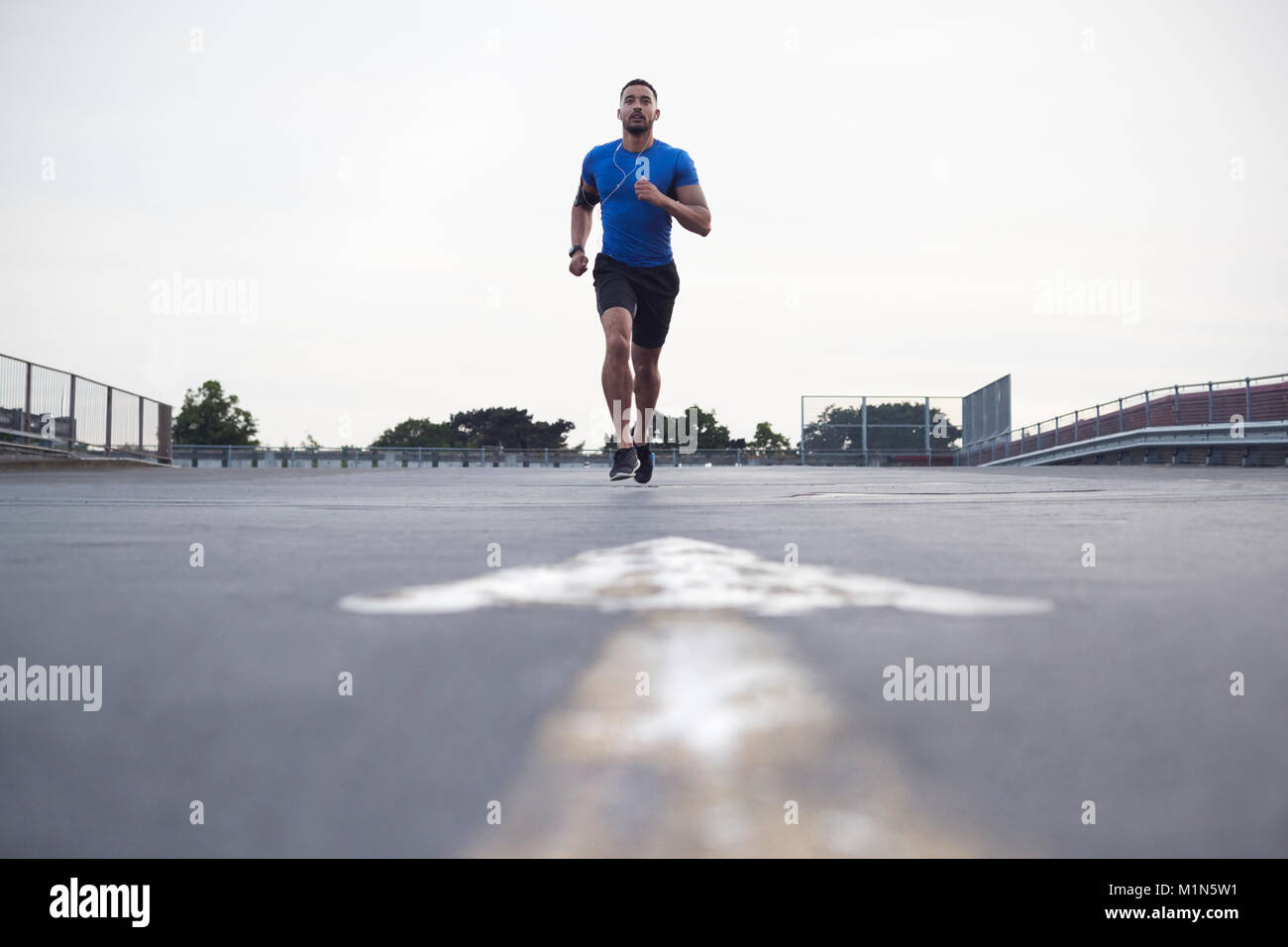 Male athlete running on a road towards camera, full length Stock Photo