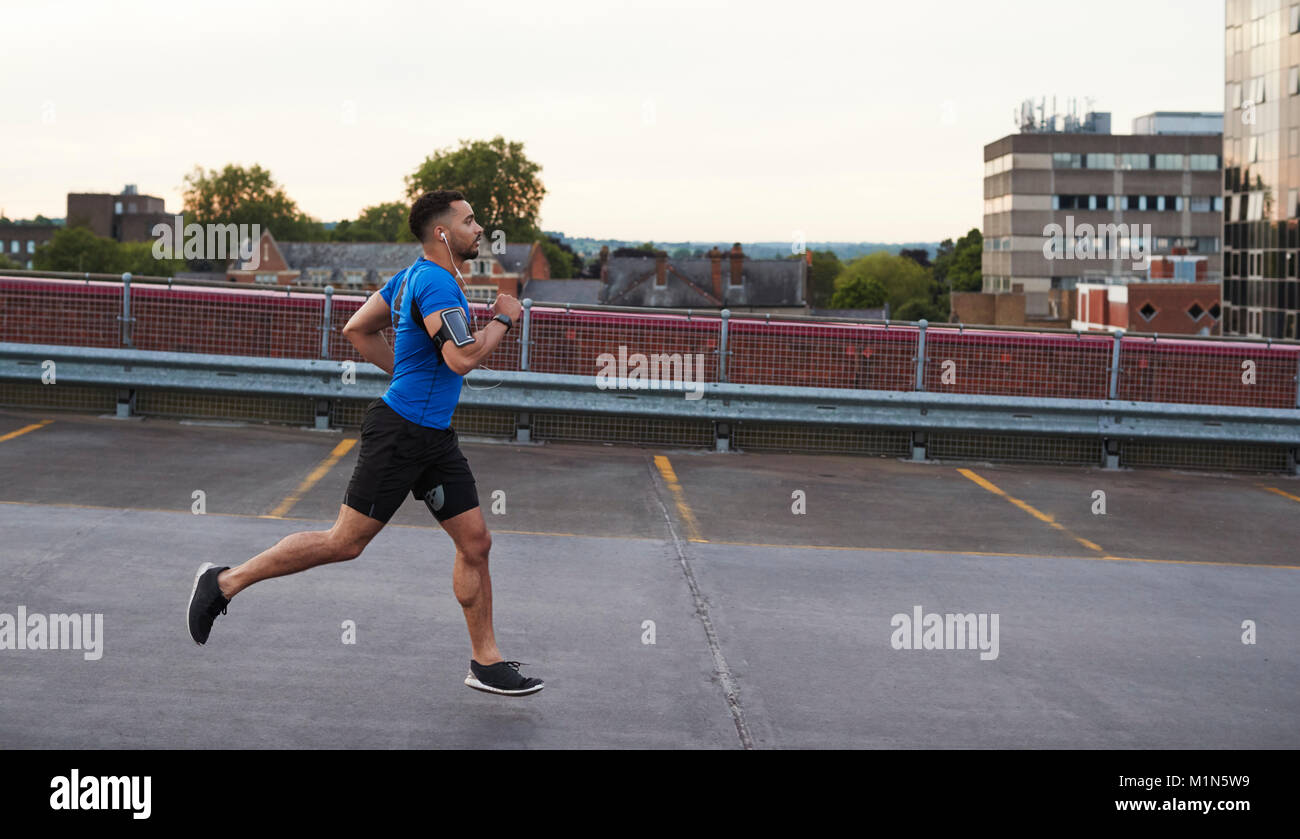 Young male athlete running on a road, side view - Stock Image
