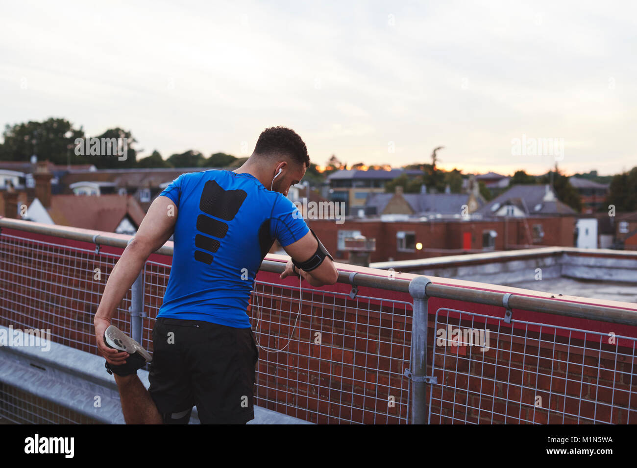 Male runner leaning on fence stretching leg in urban setting Stock Photo
