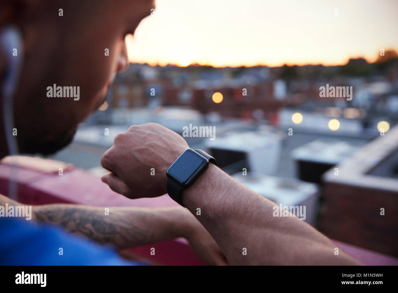 Male urban runner checks fitness app on smartwatch, close up - Stock Image