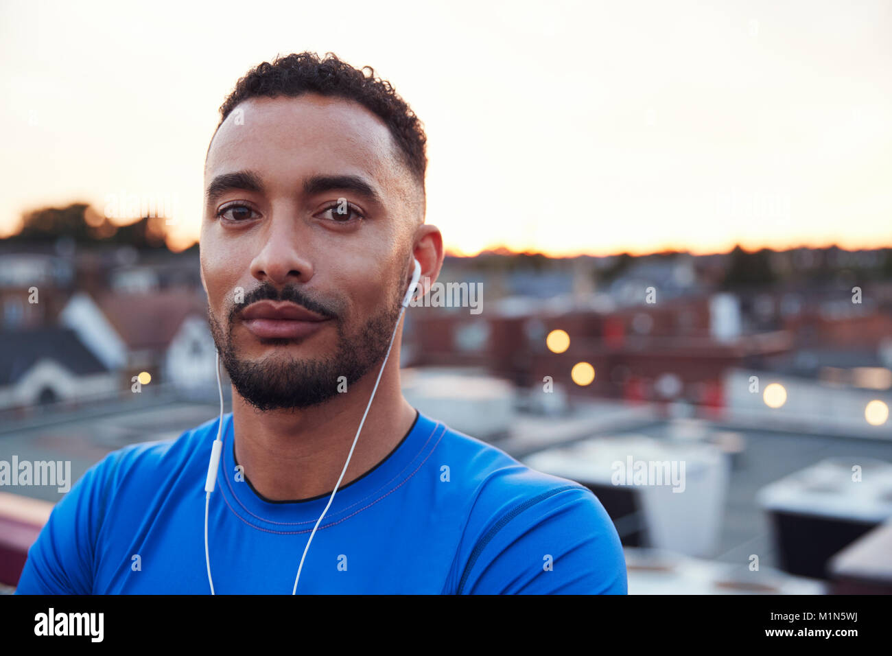 Male runner in urban setting looking to camera, close up - Stock Image