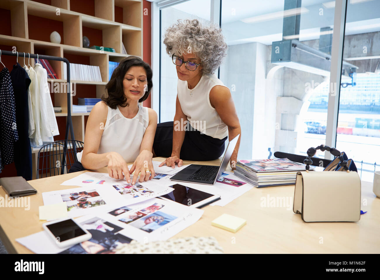 Two female creatives discussing magazine layout in an office Stock Photo