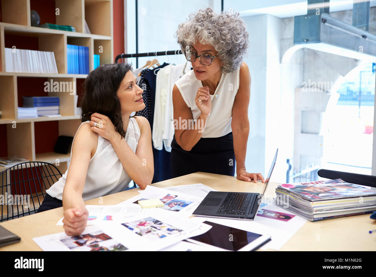 Two female creatives discussing magazine layout, close up Stock Photo