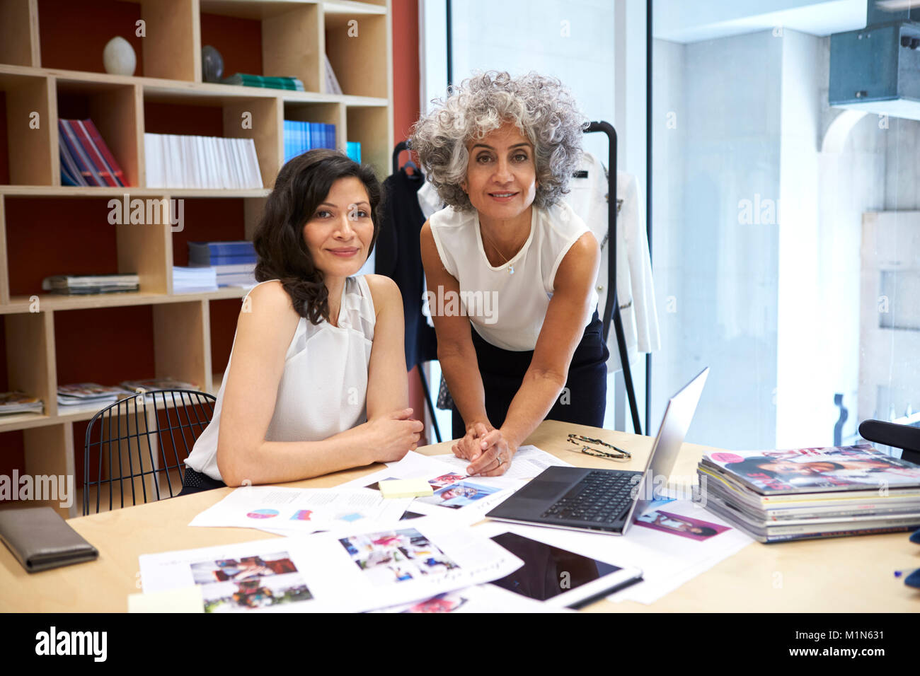 Two female creatives working in office looking to camera Stock Photo