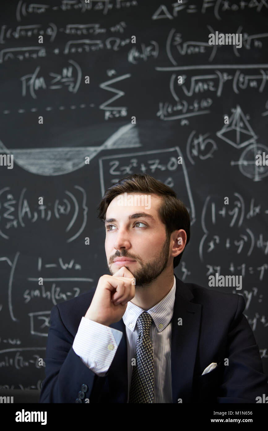 Young man contemplaiting in front of blackboard - Stock Image