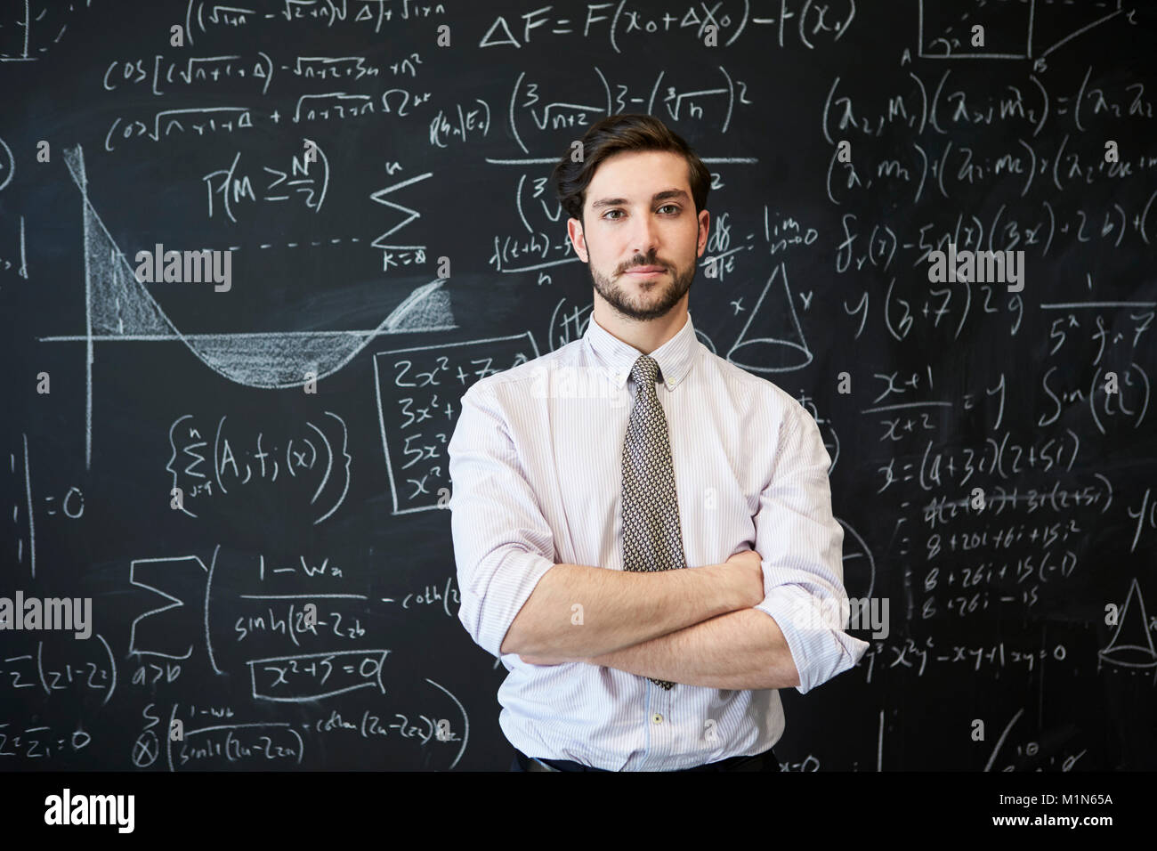 Young man looking to camera in front of a blackboard - Stock Image