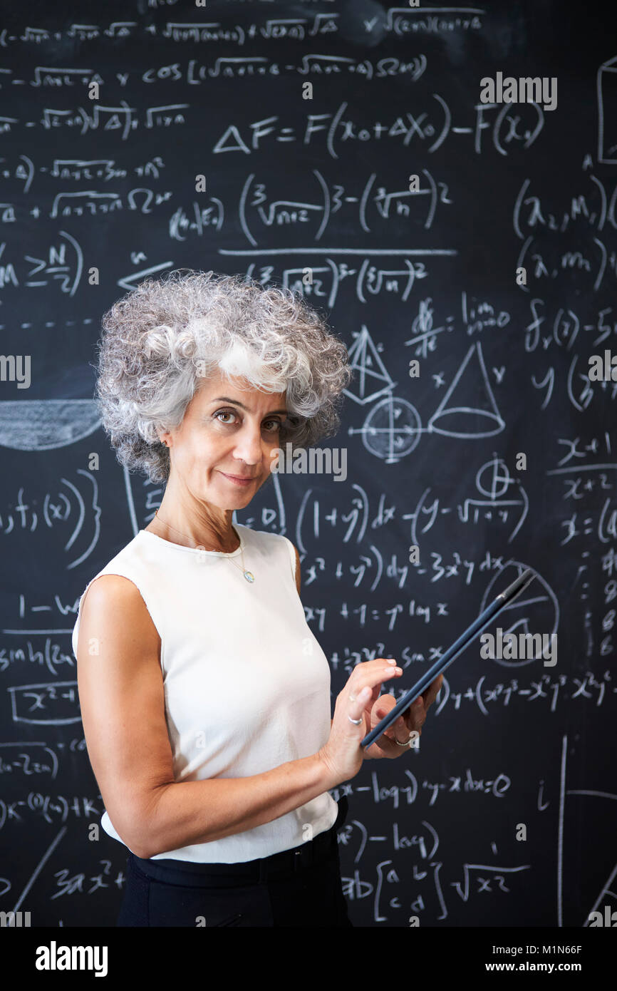 Middle aged academic woman at blackboard smiling to camera - Stock Image