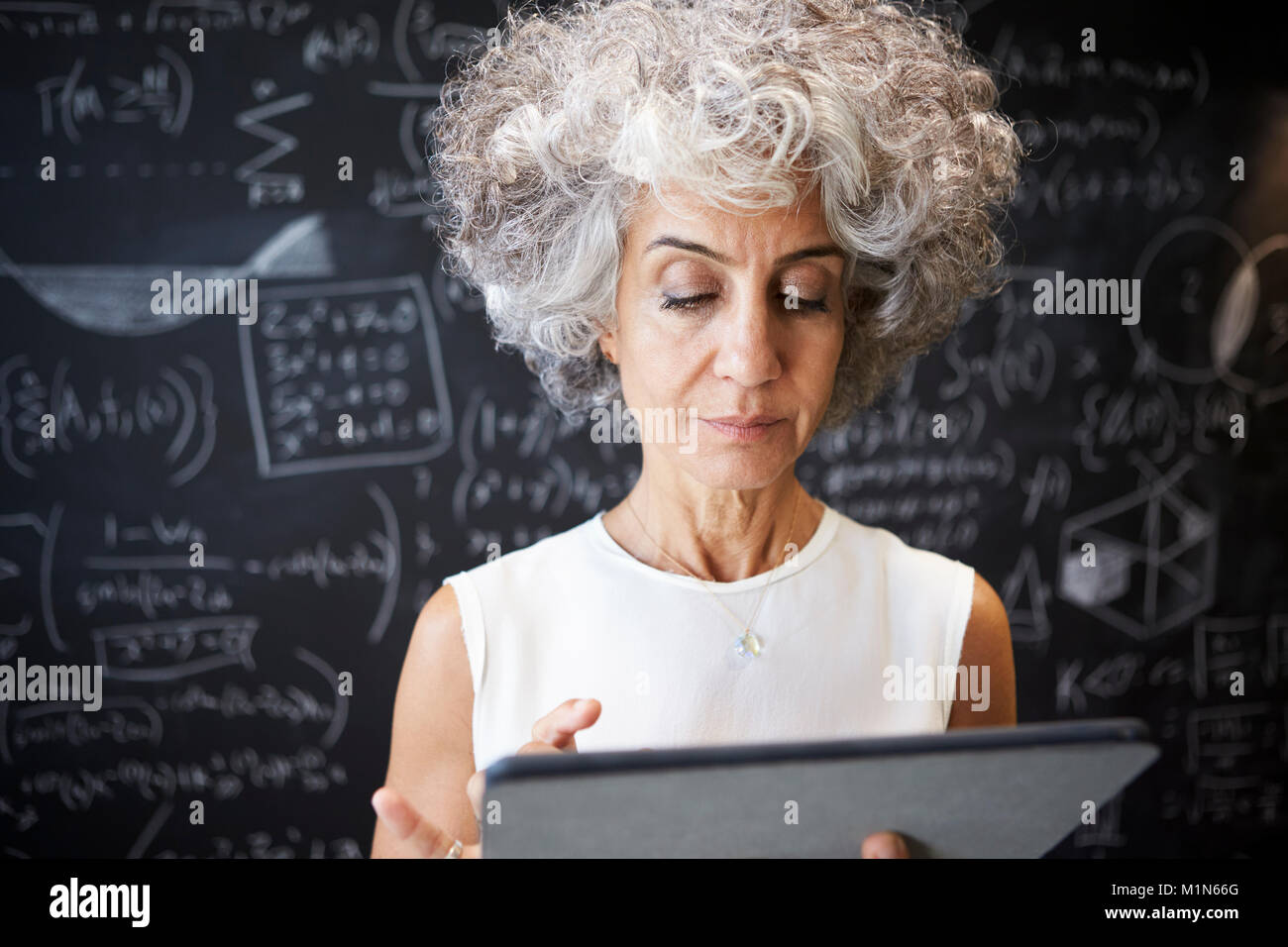 Middle aged academic woman using tablet, close up - Stock Image