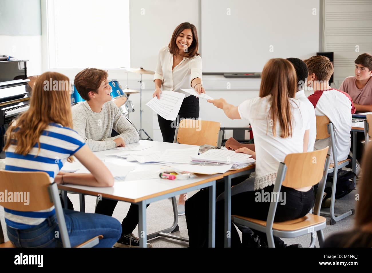 Teenage Students Studying In Music Class With Female Teacher - Stock Image