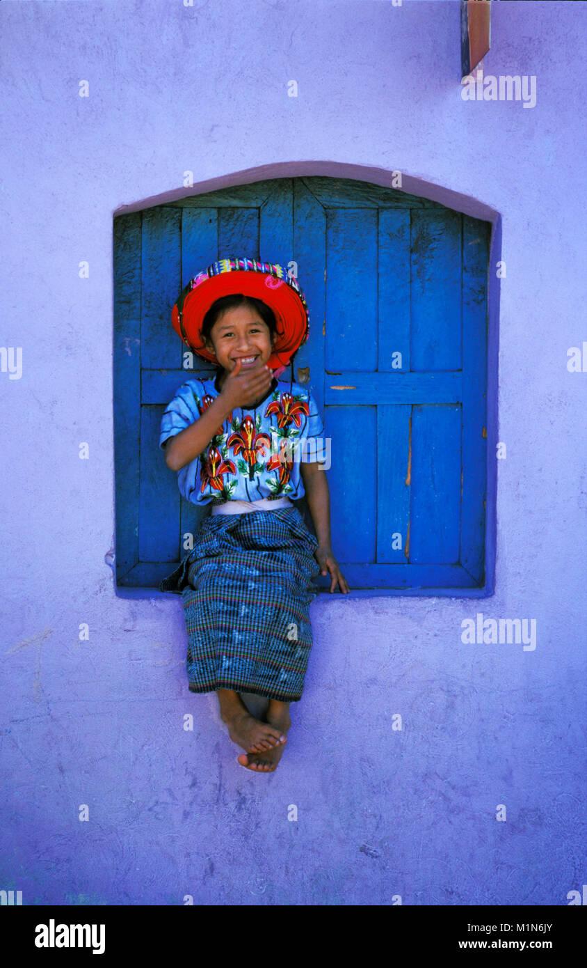 Guatemala. Santiago de Atitlšn. Lago de Atitlan. Maya girl sitting in window with typical hat. - Stock Image