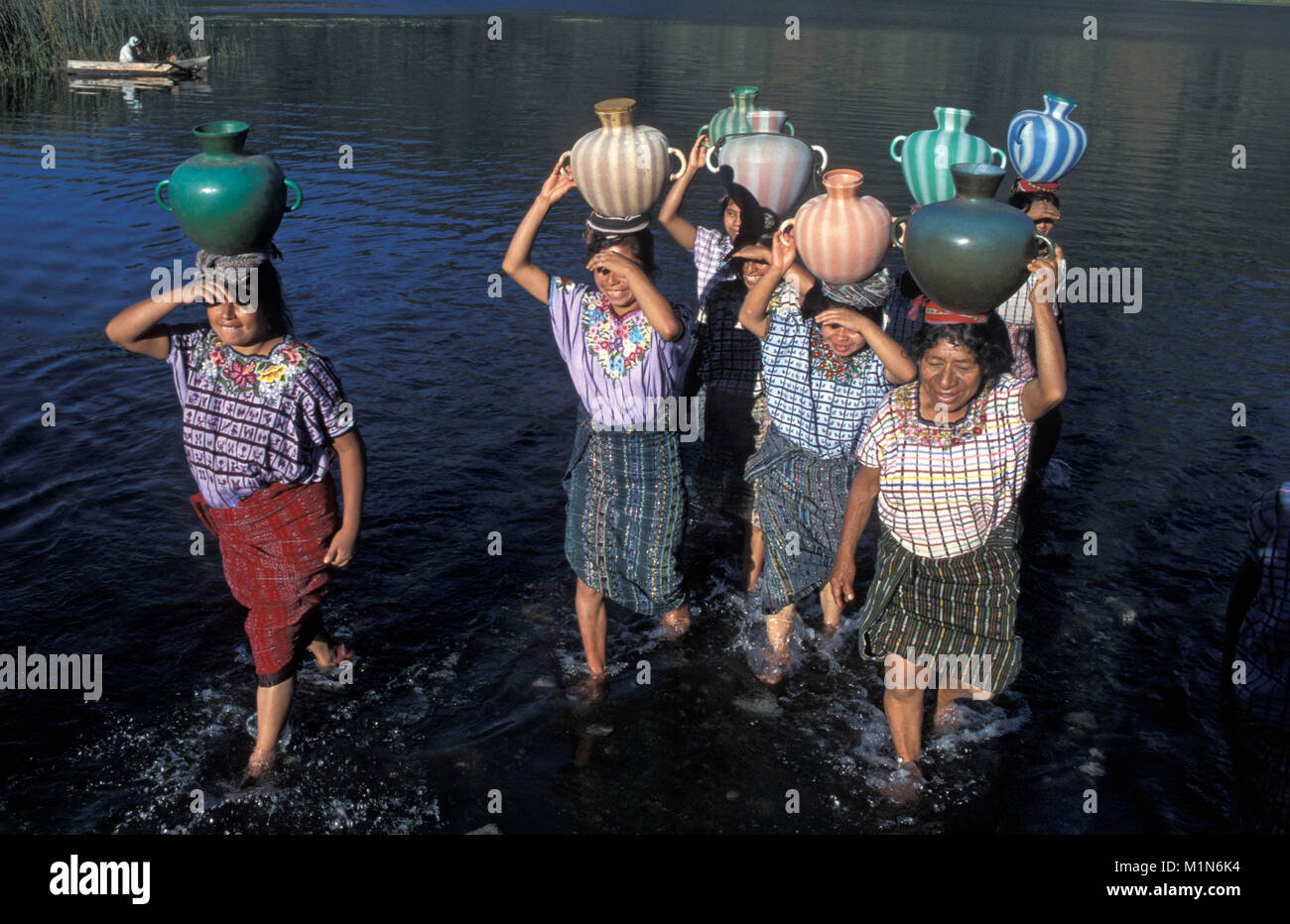 Guatemala. Santiago de Atitlšn. Lago de Atitlan. Women getting water in lake. Transport in yar on head. - Stock Image