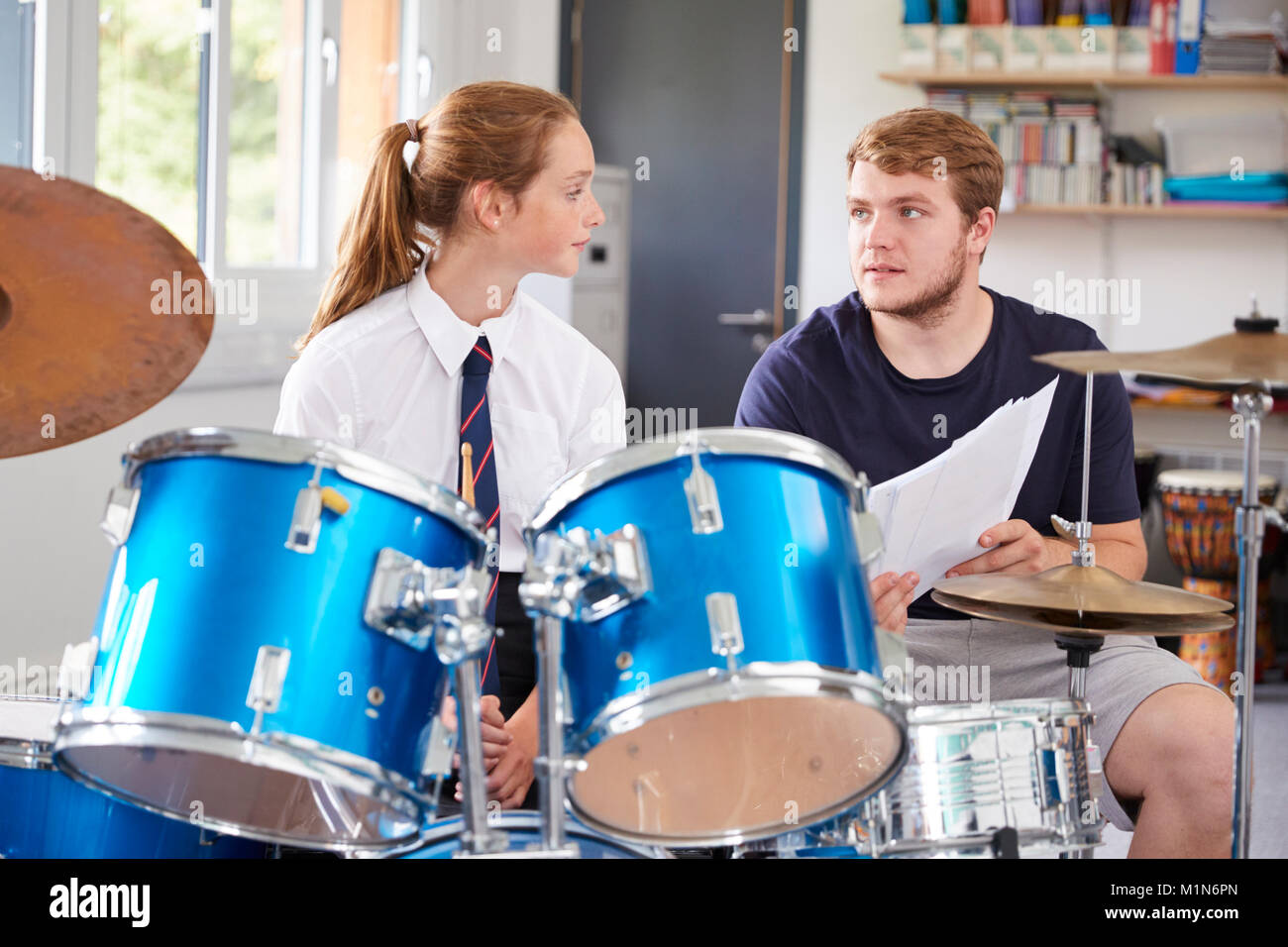 Female Pupil With Teacher Playing Drums In Music Lesson - Stock Image