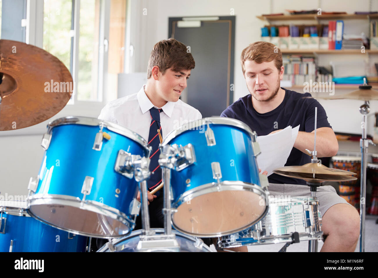 Male Pupil With Teacher Playing Drums In Music Lesson - Stock Image