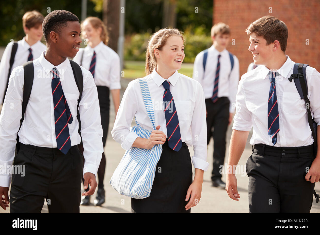 Group Of Teenage Students In Uniform Outside School Buildings - Stock Image
