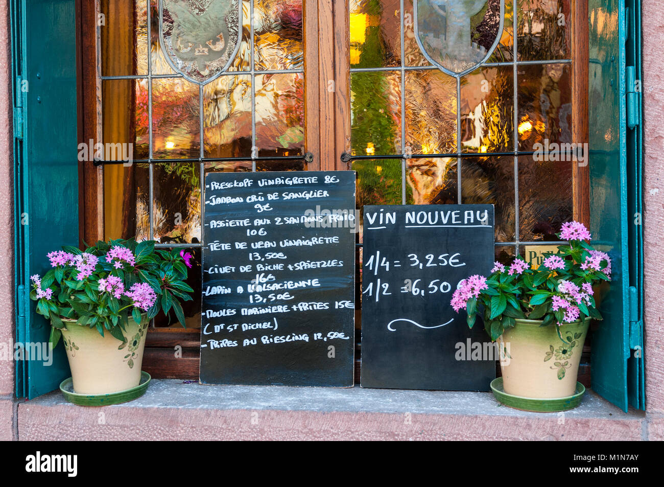 ALSACE FRANCE Blackboard menus displaying local specialties and vin nouveau outside typical inexpensive Alsace restaurant - Stock Image