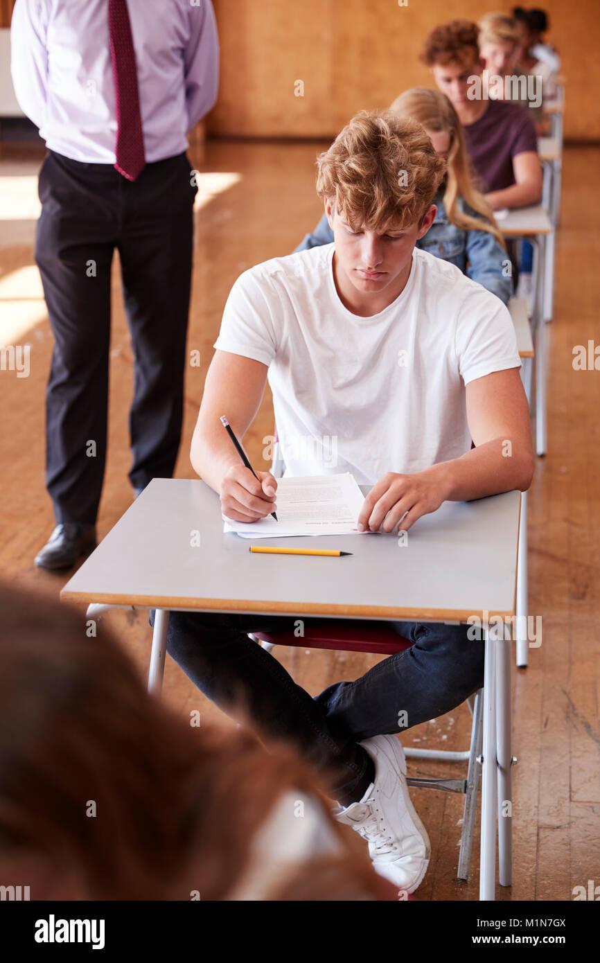 Teenage Students Sitting Examination With Teacher Invigilating - Stock Image
