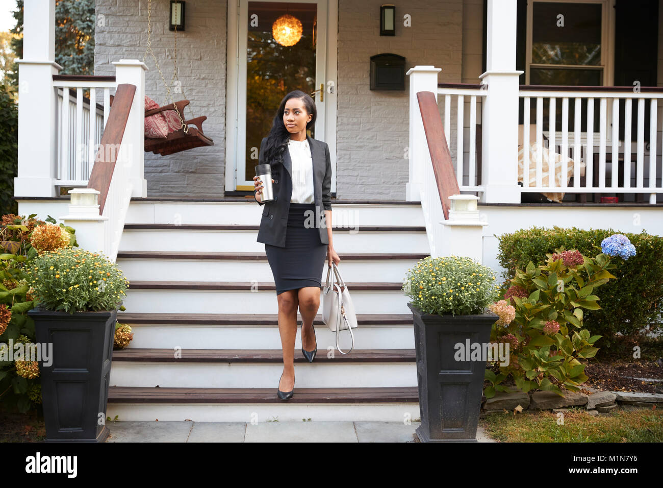 Businesswoman With Cup Of Coffee Leaving Suburban House For Work - Stock Image