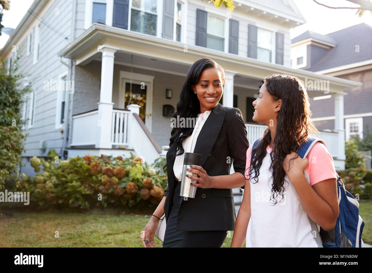 Businesswoman Mother Walking Daughter Back From School Stock Photo