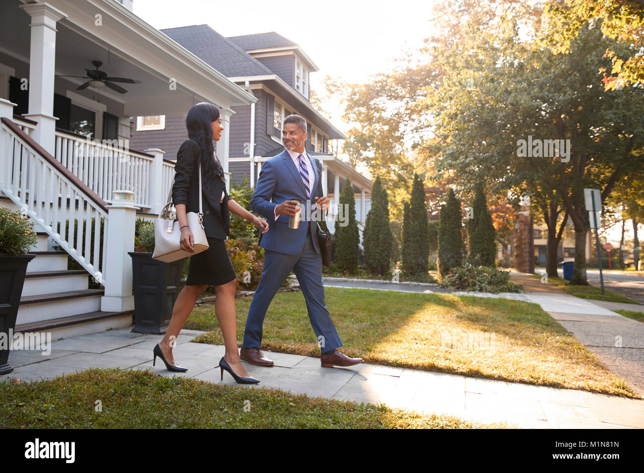 Business Couple Leaving Suburban House For Commute To Work - Stock Image