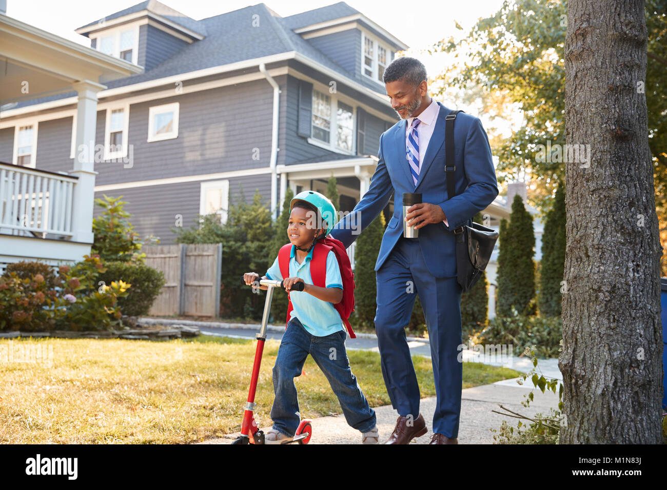 Businessman Father Walking Son On Scooter To School - Stock Image