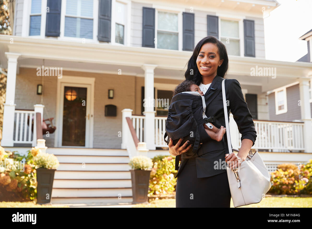 Businesswoman With Baby Son Leaving House For Work - Stock Image