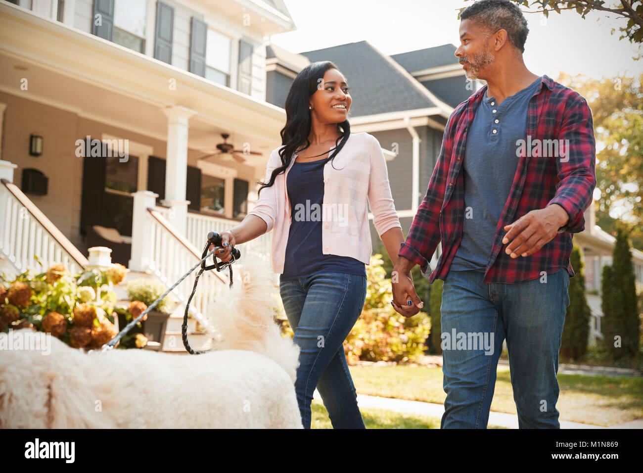 Couple Walking Dog Along Suburban Street - Stock Image