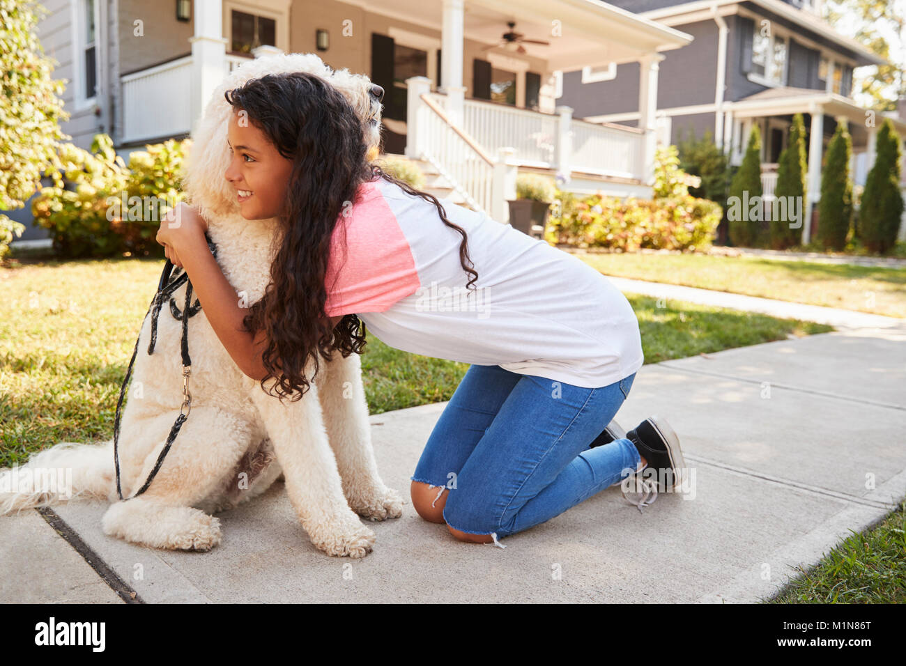 Girl Walking Dog Along Suburban Street - Stock Image