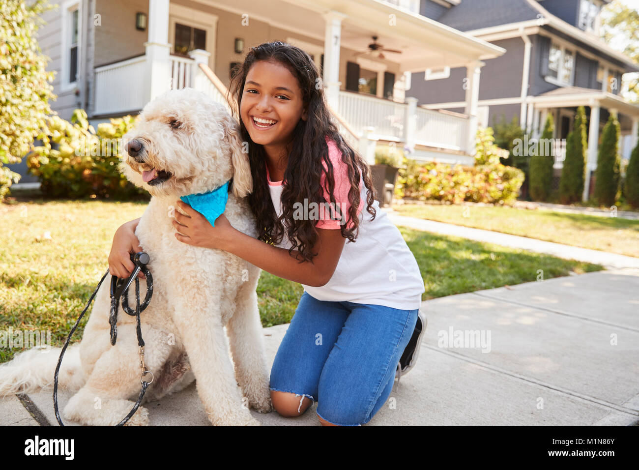 Portrait Of Girl With Dog On Suburban Street - Stock Image