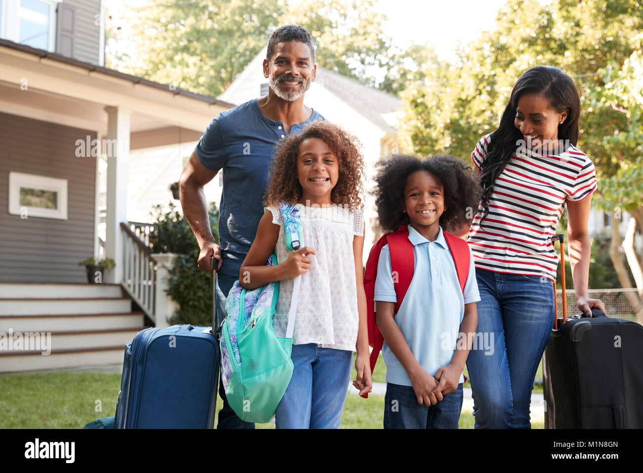 Portrait Of Family With Luggage Leaving House For Vacation - Stock Image