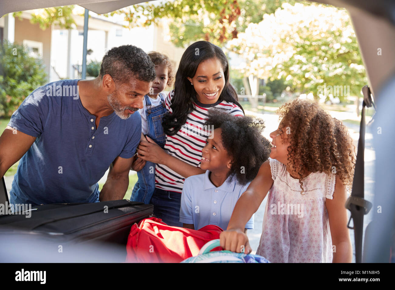 Family Leaving For Vacation Loading Luggage Into Car - Stock Image