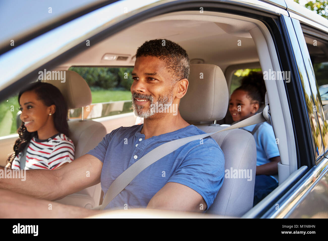 Family In Car Going On Road Trip - Stock Image