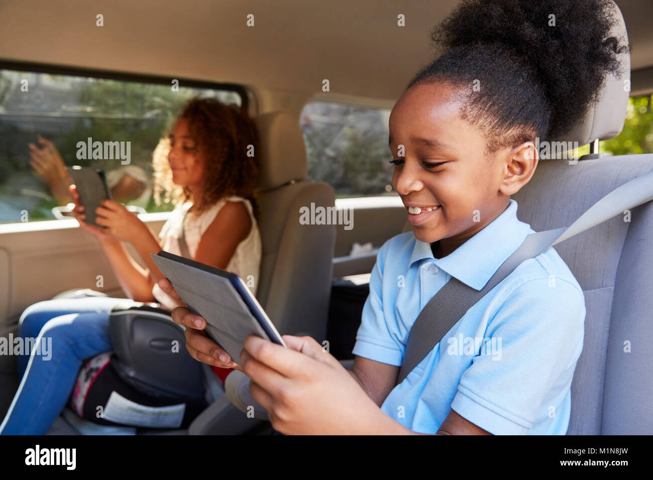 Children Using Digital Devices On Car Journey - Stock Image