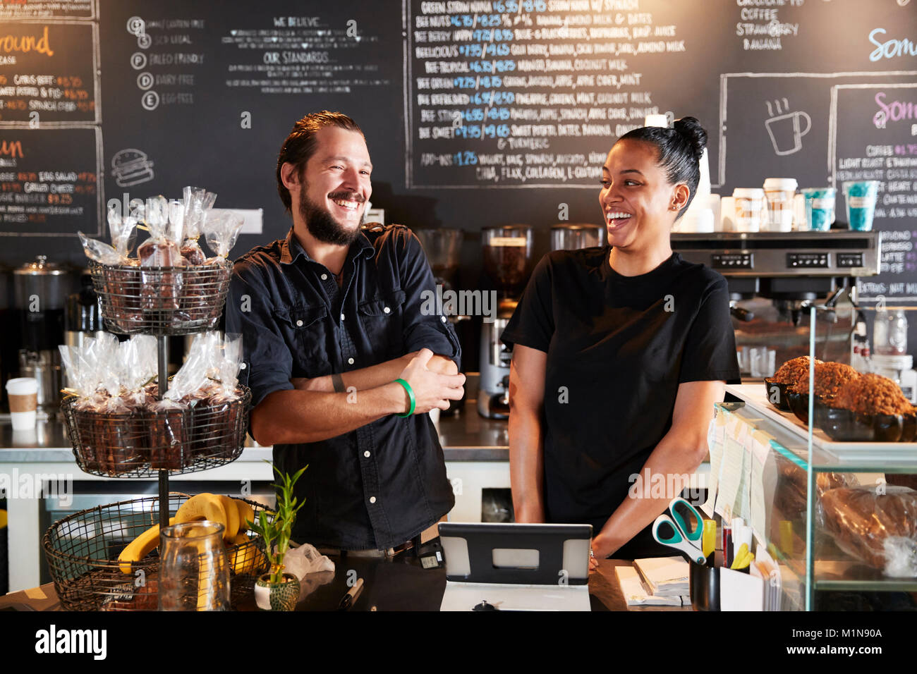 Male And Female Baristas Behind Counter In Coffee Shop - Stock Image