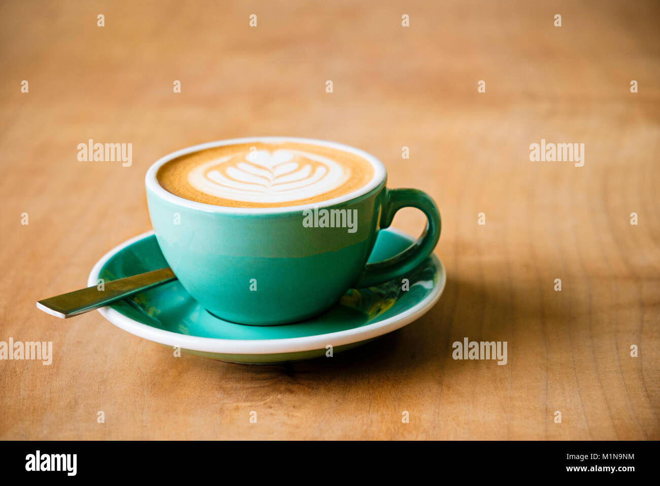 A cup of coffee with latte art of a leaf in the foam with a spoon on a wooden table - Stock Image