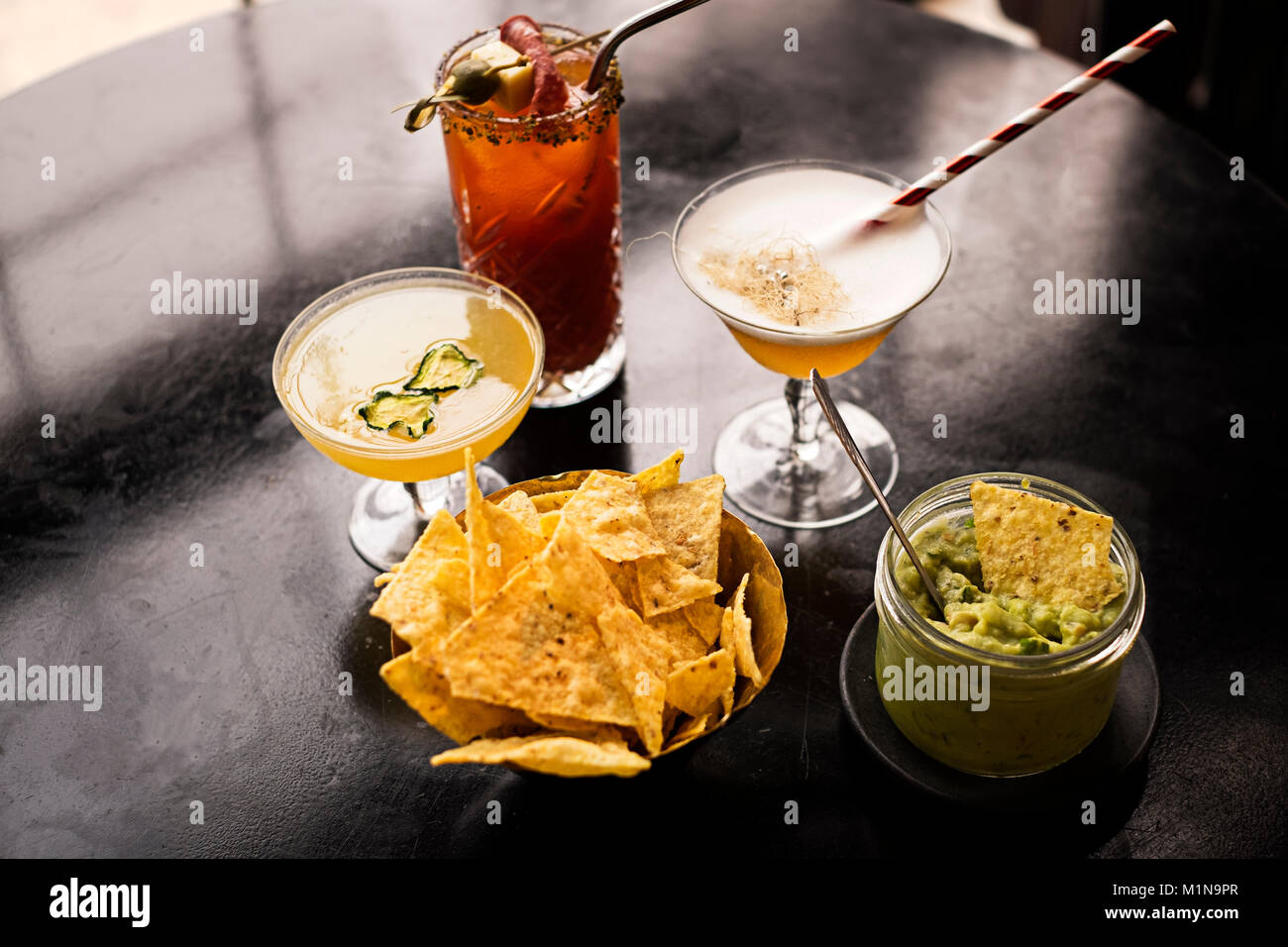 Trio of classic cocktails served with tortilla chips and guacamole. - Stock Image