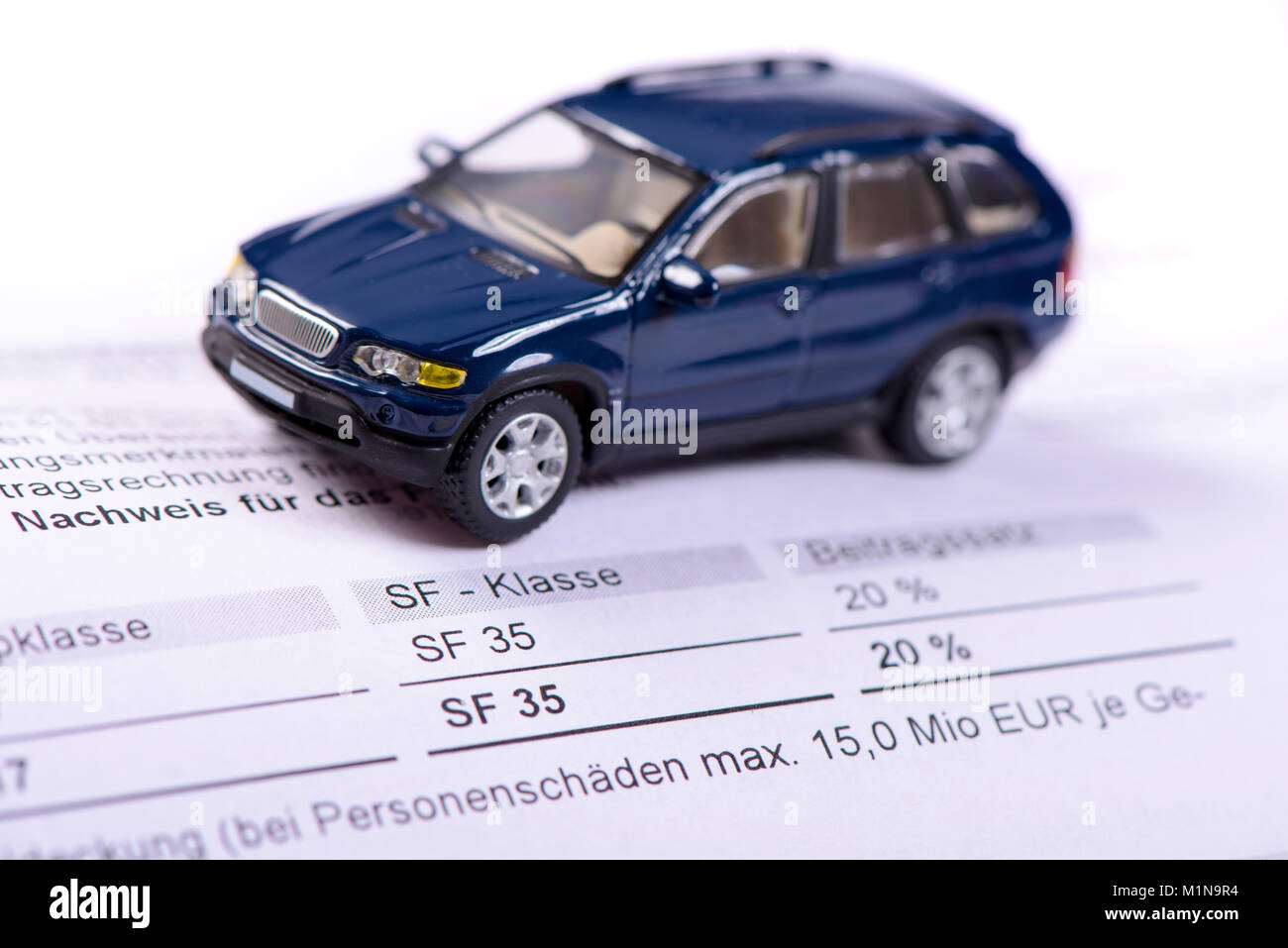 KFZ Versicherung mit Rechnung und Modellauto - Stock Image