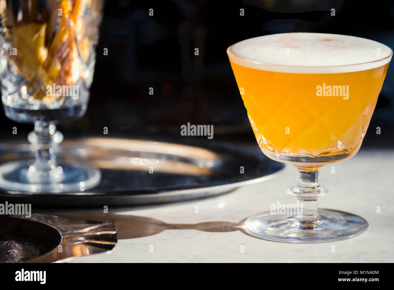 Gin & Tonic cocktail with foam garnish in a cut glass cocktail glass. - Stock Image