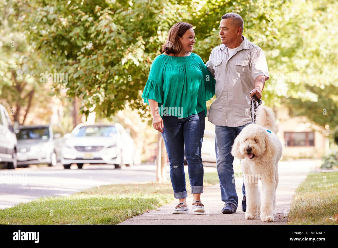 Senior Couple Walking Dog Along Suburban Street - Stock Image
