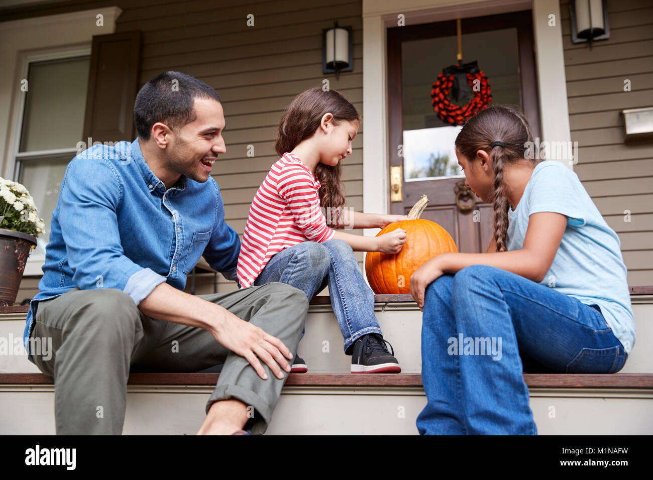 Father And Daughters Drawing Face On Halloween Pumpkin - Stock Image