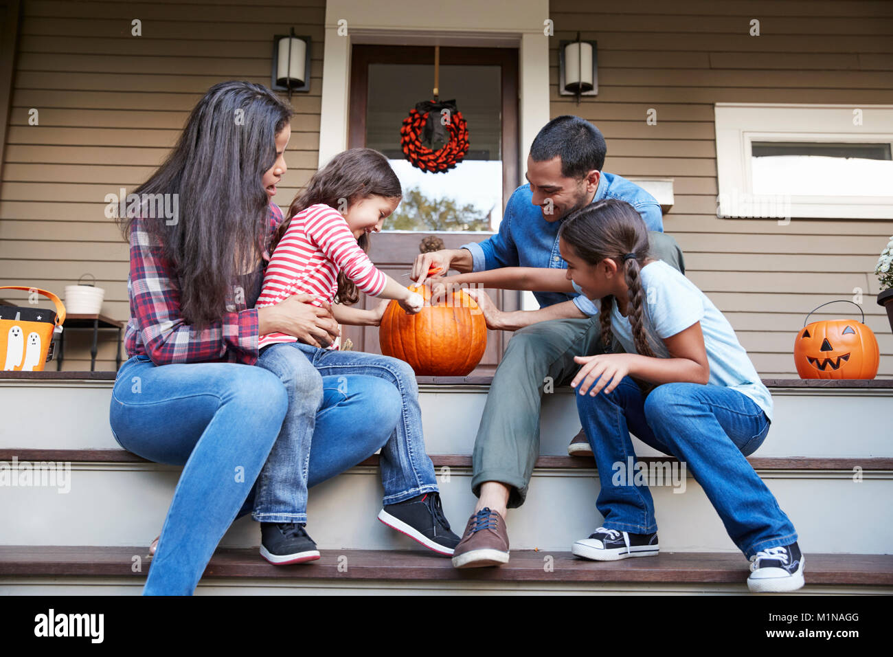 Family Carving Halloween Pumpkin On House Steps - Stock Image
