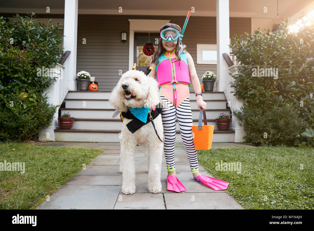 Girl With Dog Wearing Halloween Costumes For Trick Or Treating - Stock Image
