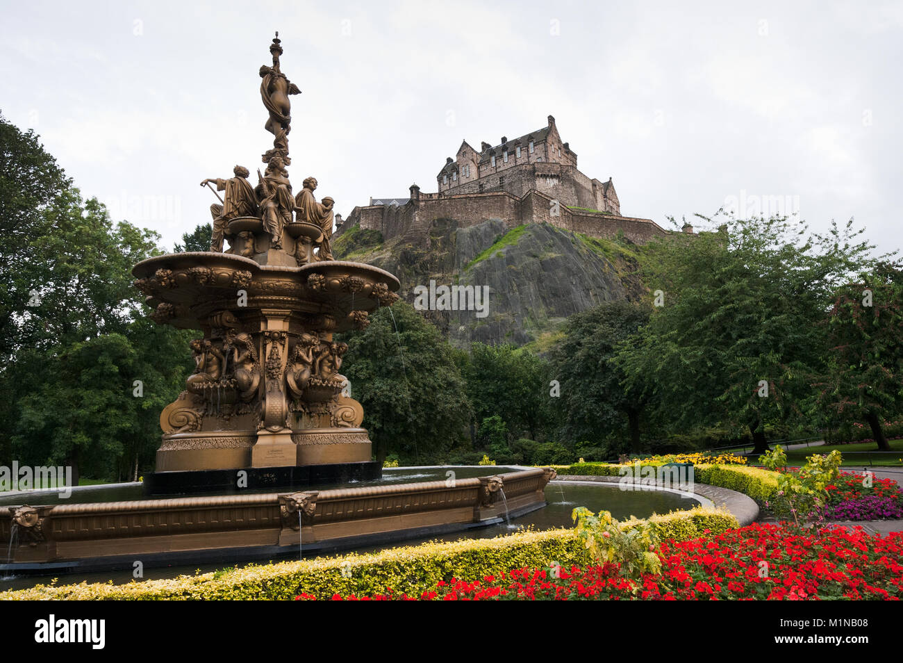 View of Edinburgh castle from princess gardens with the famous fountain. - Stock Image