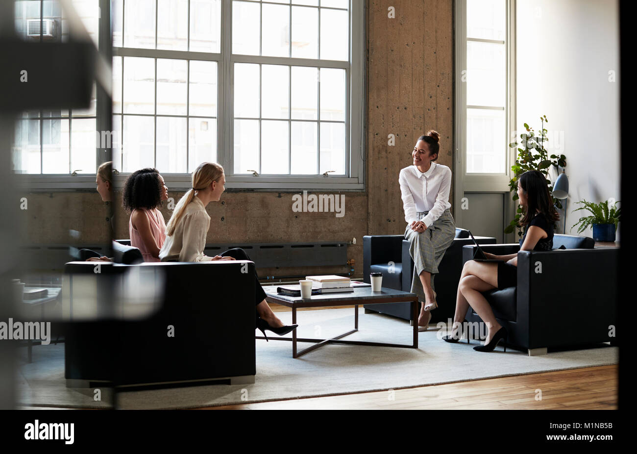 Seated female manager talking to team at an informal meeting - Stock Image