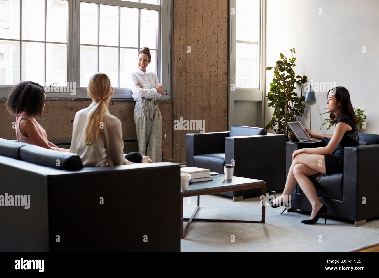 Standing female manager with arms crossed at casual meeting - Stock Image