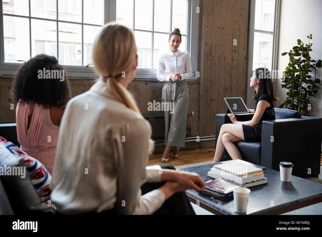 Standing female manager talking to team at casual meeting - Stock Image