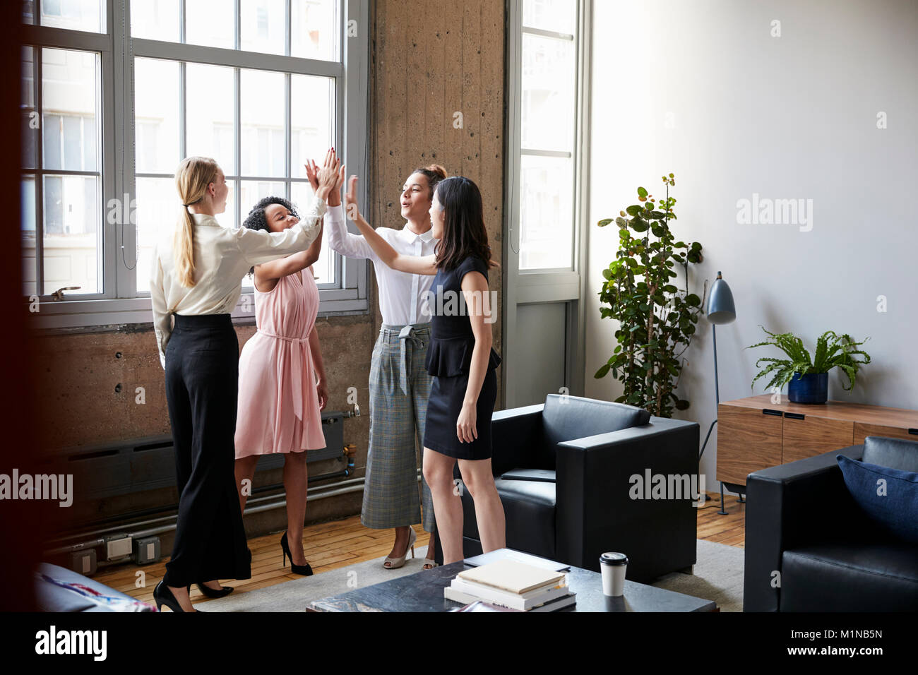 Female colleagues high five at a motivational meeting - Stock Image