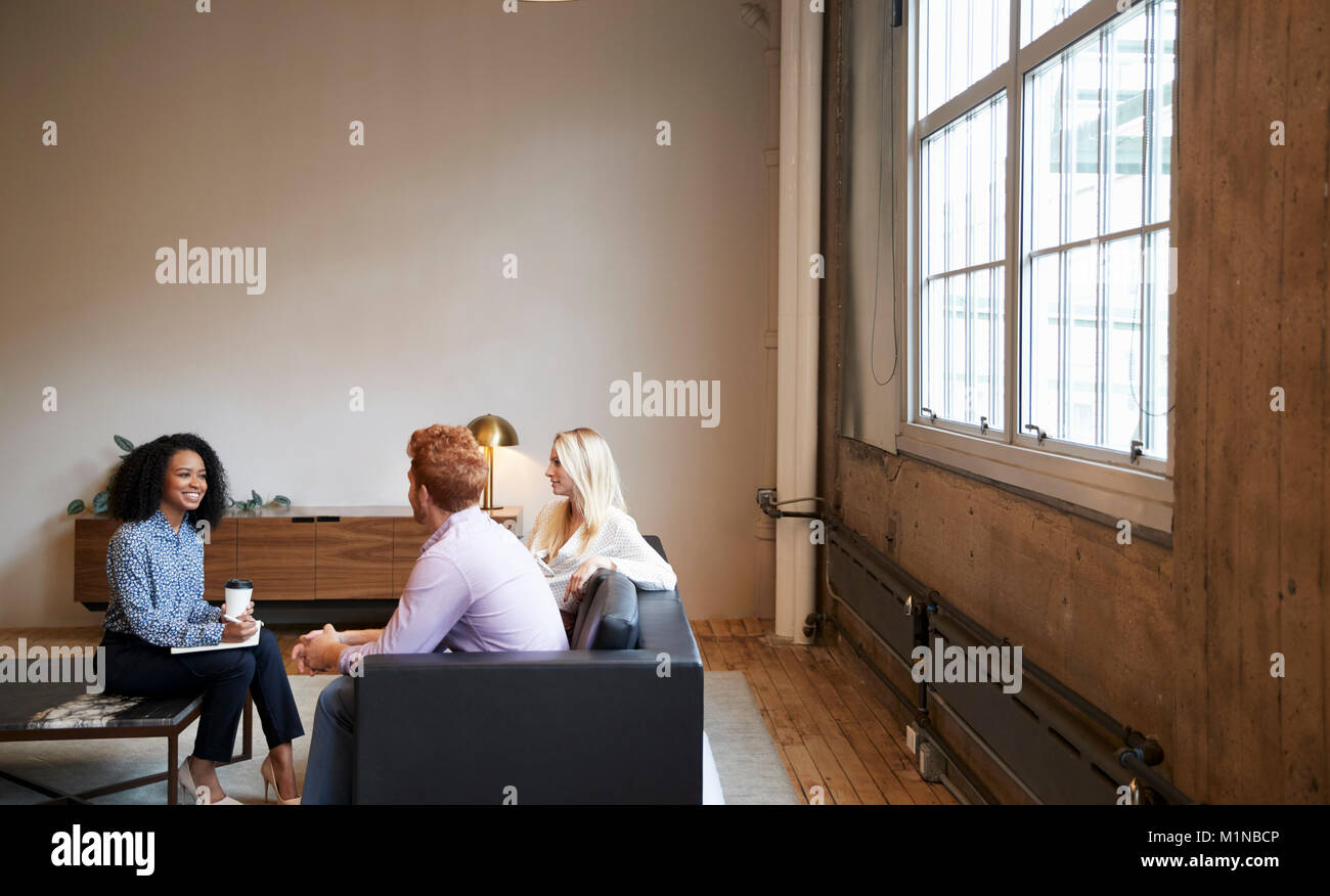 Three colleagues at a casual work meeting in a lounge area - Stock Image