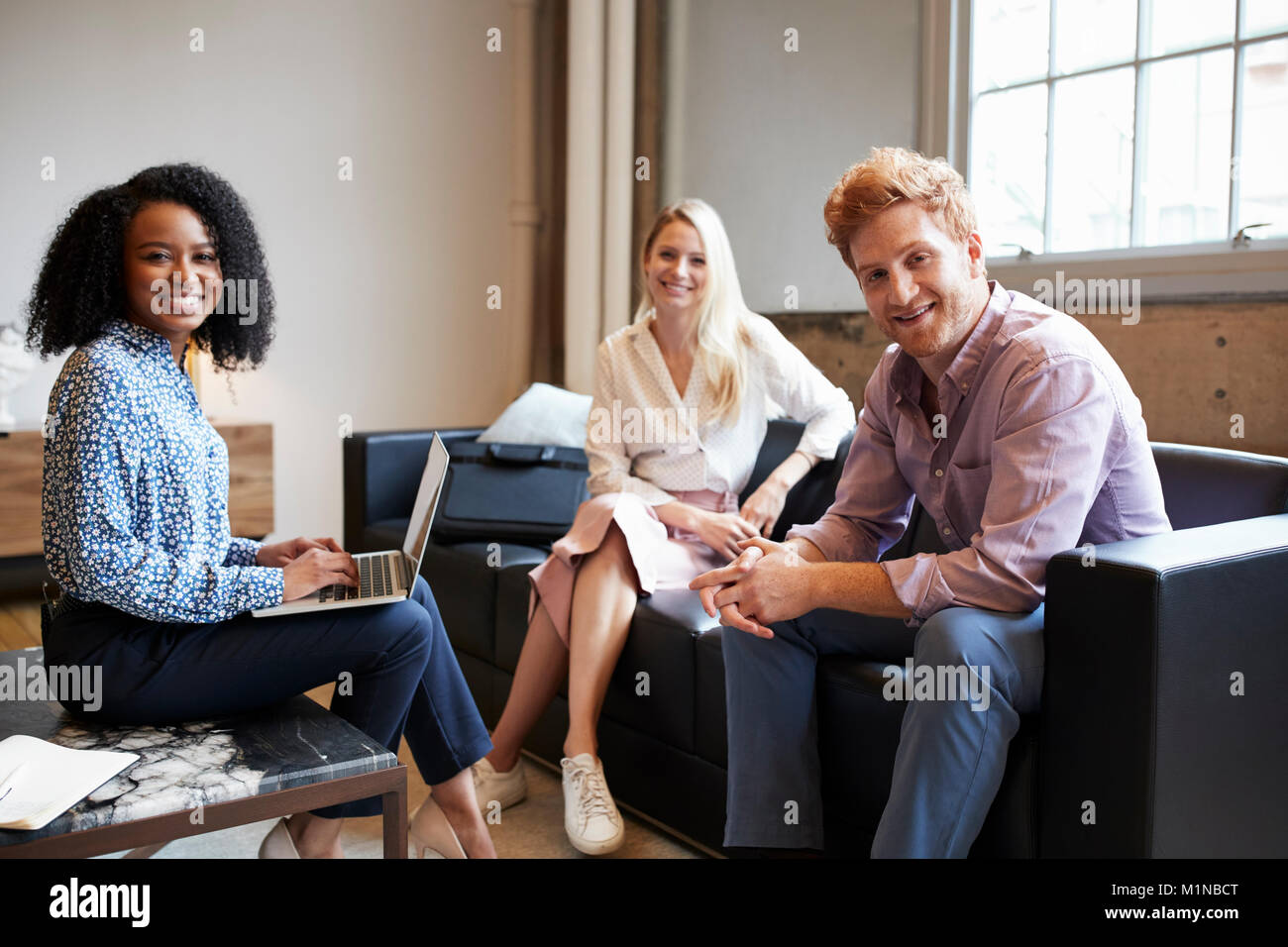 Three young colleagues at a casual work meeting look to camera - Stock Image